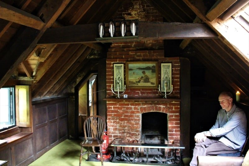 A man sitting in front of a fireplace in the attic at Clouds Hill.