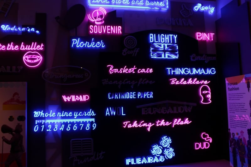 A neon display shows army words lit up.