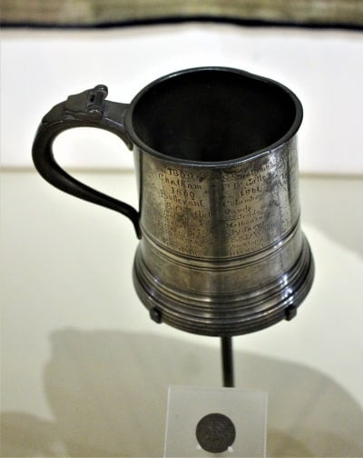 A glass bottomed tankard and a Kings shilling.