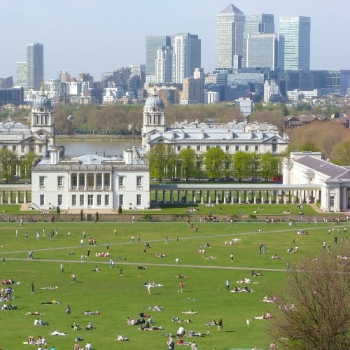 A view over Greenwich Park with people on the lawn.