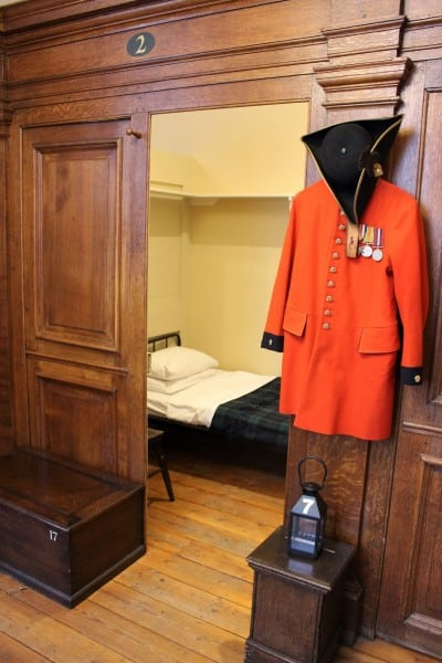 The outside of a small wooden room with a uniform hanging outside.