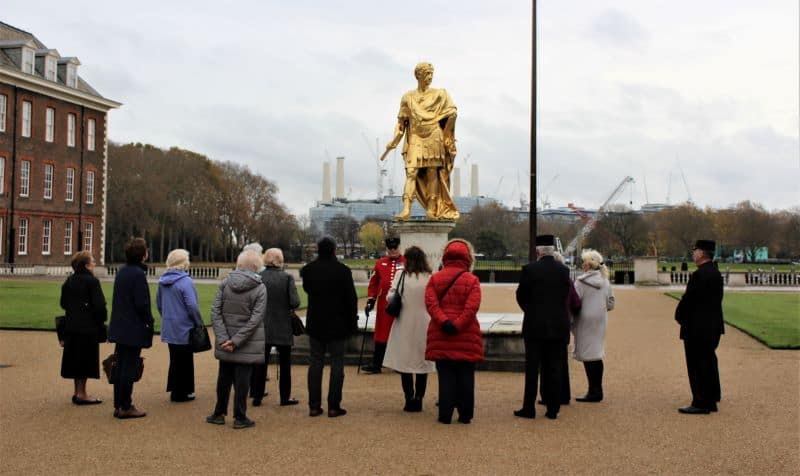 A tour group standing in front of a gold statue.