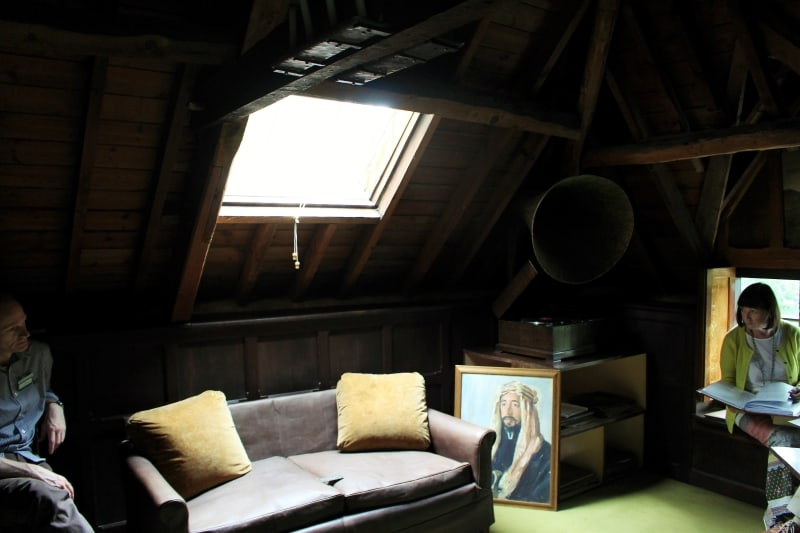 Two people sitting in an attic room.