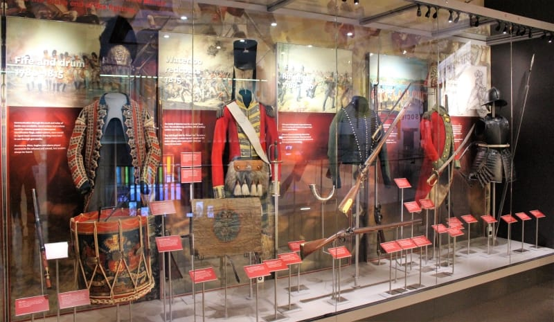 A row of soldiers uniforms in a glass case in the National Army Museum.
