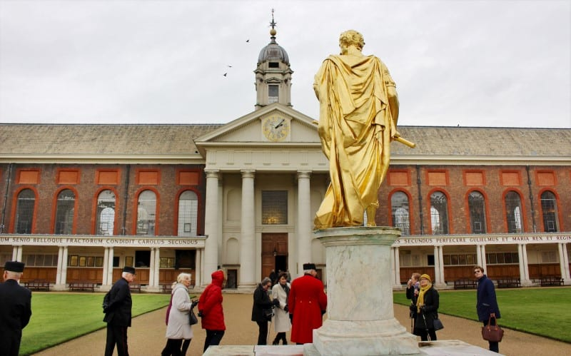 A tour group standing behind a golden statue at the Royal Chelsea Hospital