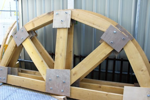 A wooden arch leaning up against a container.