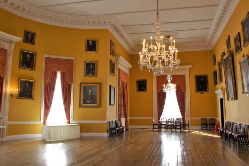 Inside the banqueting hall with orange walls, wood floor and portraits.