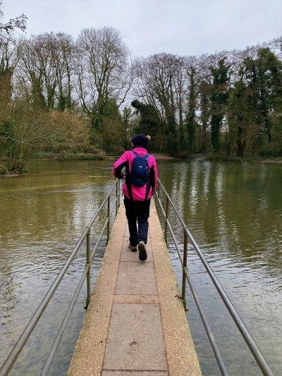 A person walks over a narrow bridge over a flooded River Frome.