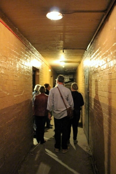 A tour group walking down a dark and narrow passageway.