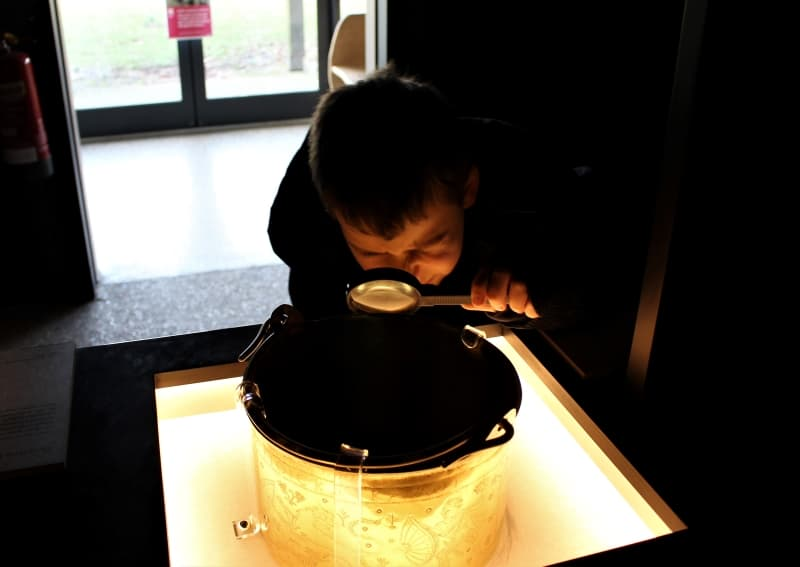A boy examining a Byzantine bowl with a magnifying glass.