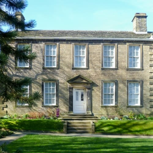 The outside of the Bronte Parsonage Museum in the sunshine.