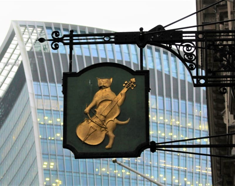 A close up of a hanging sign showing a cat playing a fiddle.