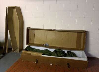 A MDF coffin standing up and one of cardboard lying down.