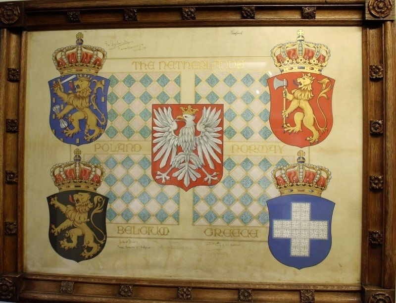 A framed document with heraldic shields on it