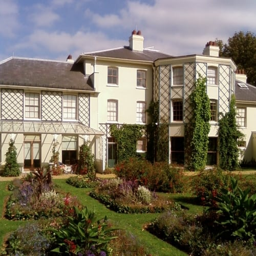 The exterior of Charles Darwins House surrounded by gardens and flowers.
