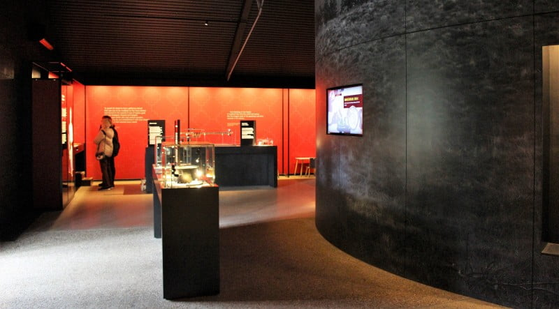 The exhibition space at Sutton Hoo with people looking at displays.