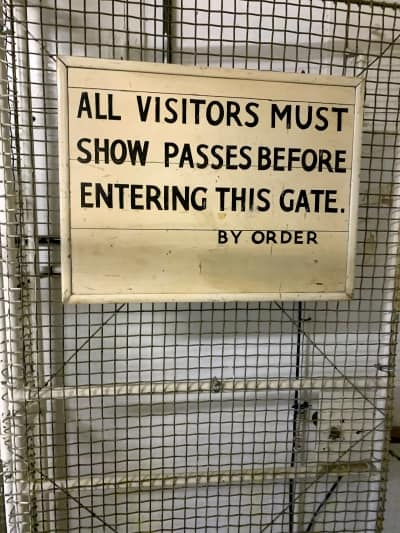 An old sign on a gate saying 'All visitors must show passes'.