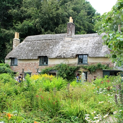 The outside of Thomas Hardy's cottage in Dorset surrounded by a garden.