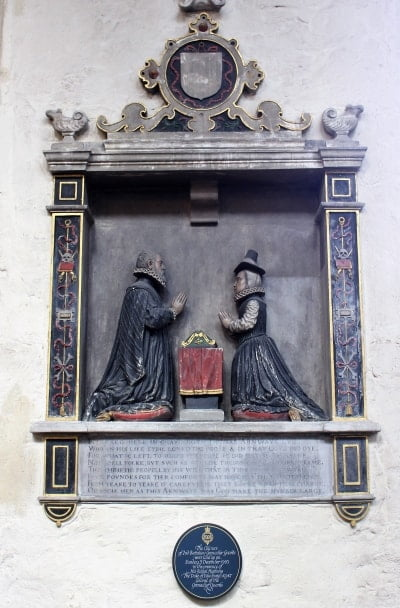 A wall memorial with two figures praying.