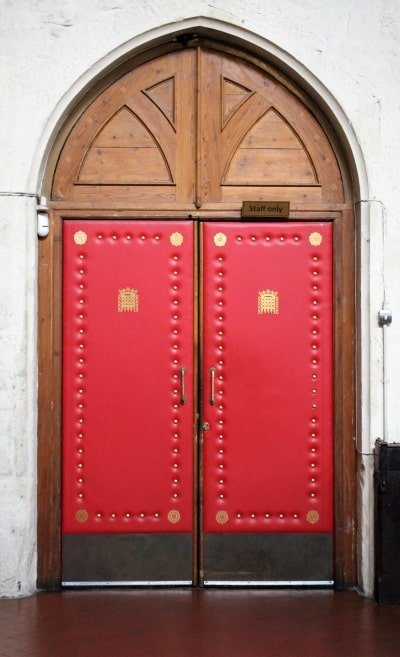 The red padded door with the House of Commons portcullis on it.