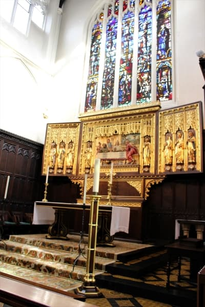 The golden reredos and stained glass window on east wall of St Margarets Church.