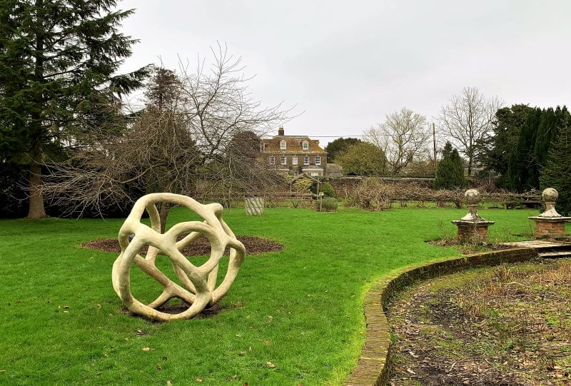 Art work in the Walled Garden with Moreton Manor in the background