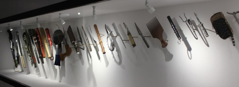 A row of  homemade weapons in a glass case.