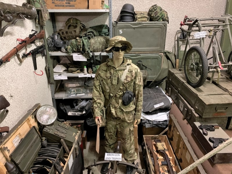 A mannequin in army uniform surrounded by assorted weapons.