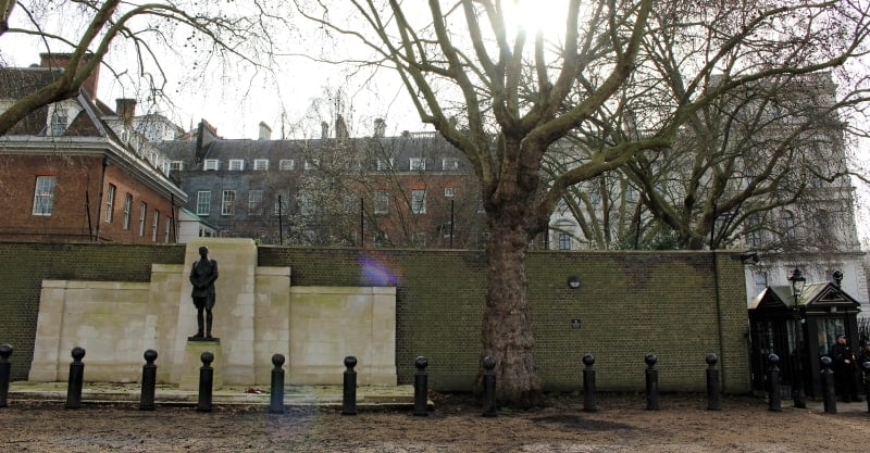 The back view to Downing Street with a statue in front of a wall topped with barbed wire.