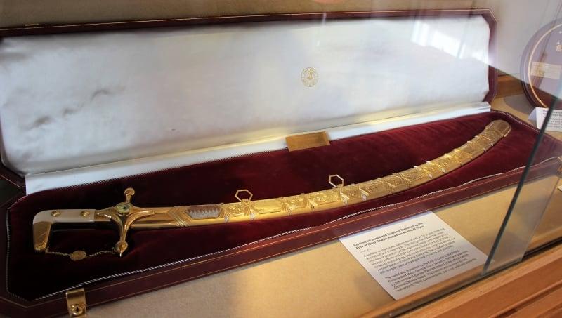 A golden sword inside a red velet display case.
