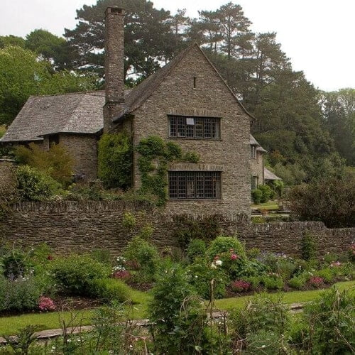 The exterior of Coleton Fishacre surrounded by a large garden.
