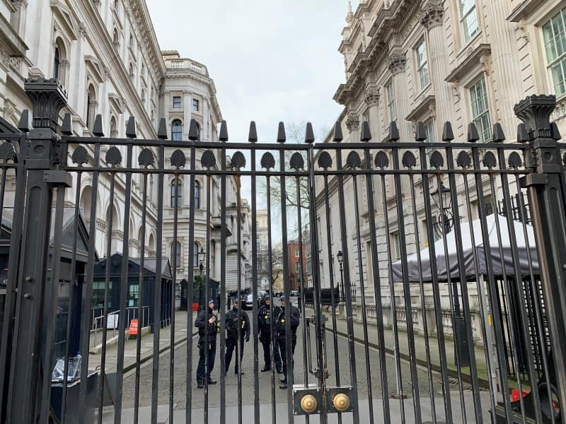 Looking through the gates to Downing Street, with police and cars behind them.