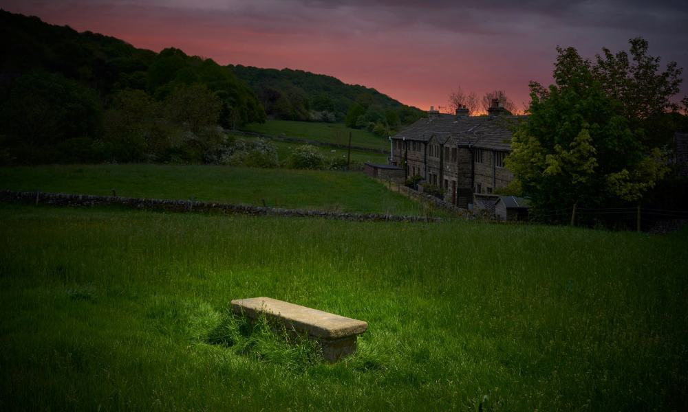 A singla table grave on a hillside behind some cottages.