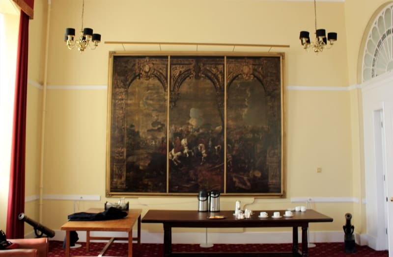 Inside the Marlborough Room at Sandhurst showing the old painting behind a table.