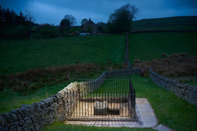 Mompessons well in the village of Eyam surrounded by a stone wall and railings.