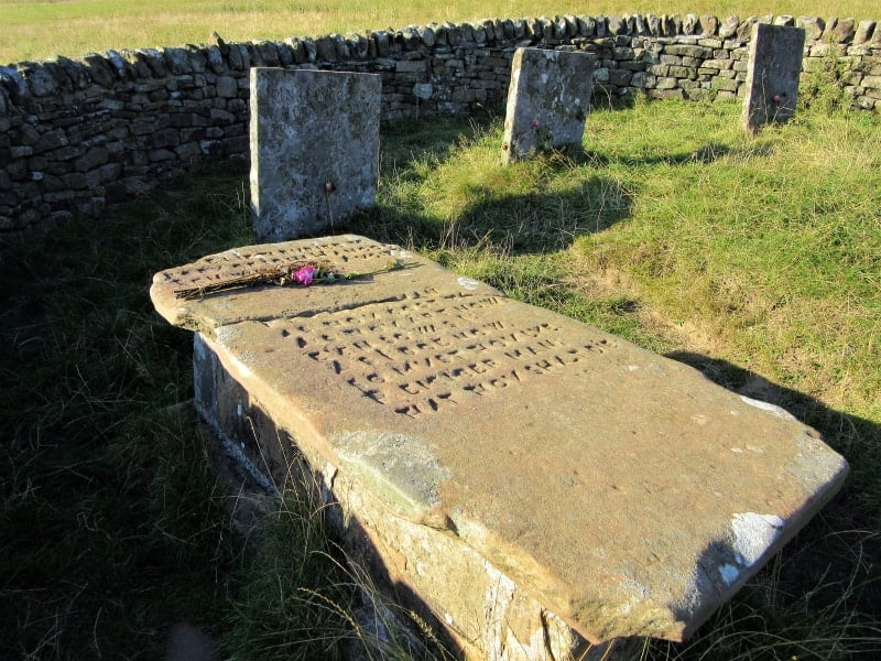 A low stone wall with a sign saying 'Riley Graves' on the side int he village of Eyam.