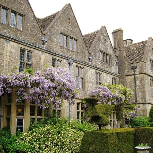 The exterior of Rodmarton Manor covered in wisteria flowers.