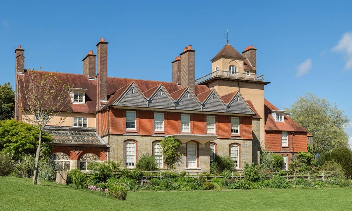 An exterior view of the front of Standen House on a sunny day.