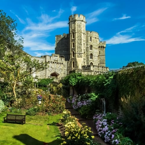 The outside of Windsor Castle and gardens on a sunny day.
