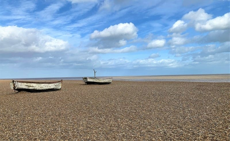 Two wooden boats on the stone beach against a blue sky.
