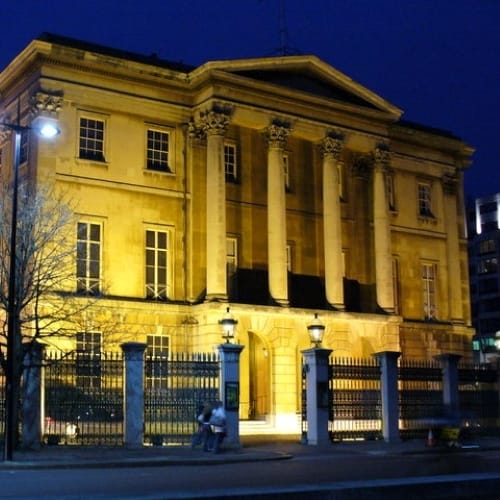 The exterior of Apsley House lit up at nighttime.