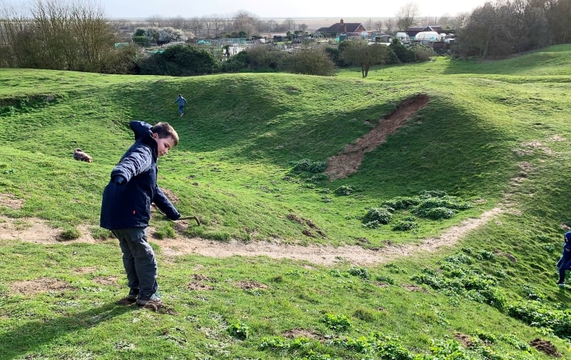 Kids playing in the earthworks at Orford Castle.