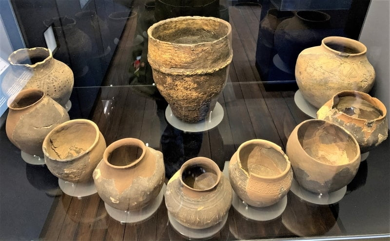 A display case containing cremation urns in a semi circle.