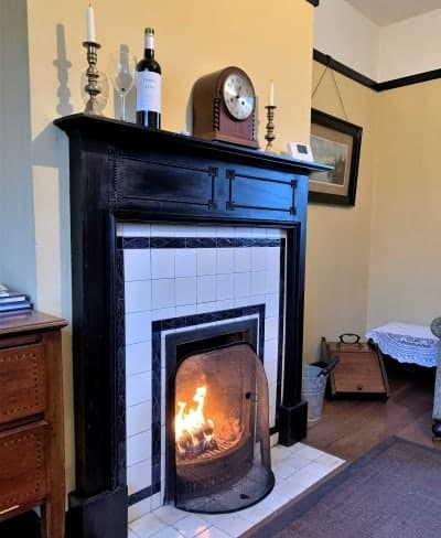 A close up of a tiled fireplace with a fire lit.