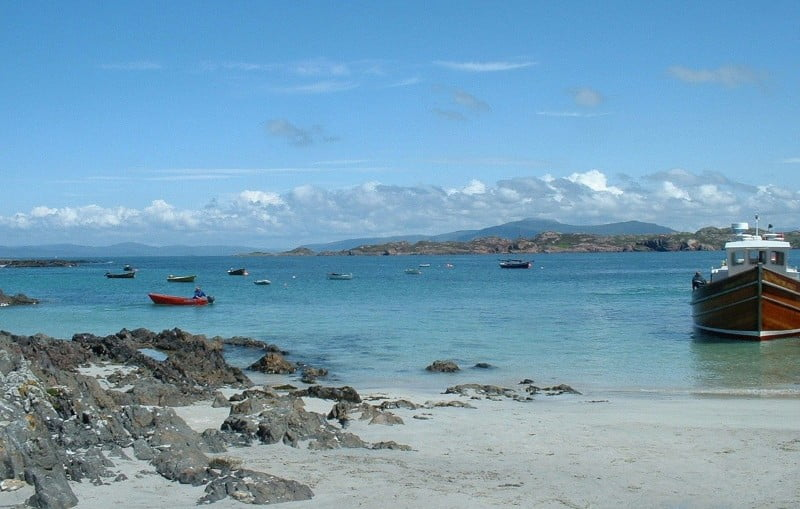 The beach on Iona with blue sea and sky and a boat on the water.