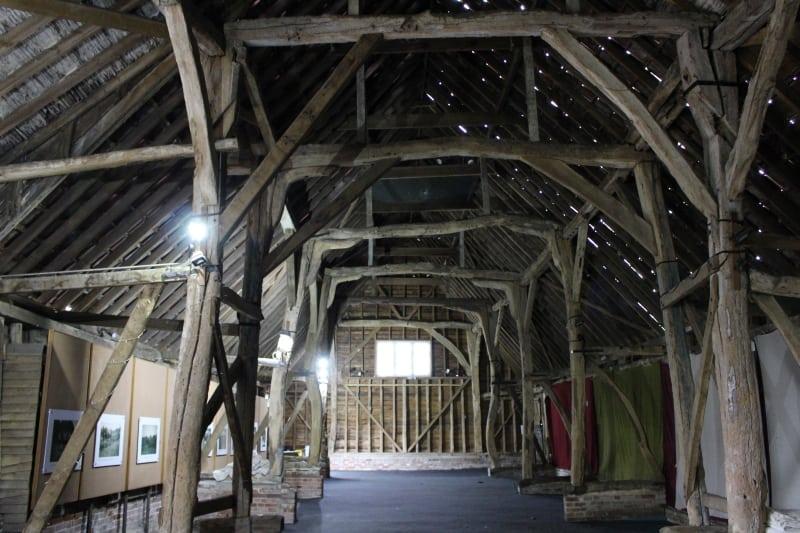 The inside of a huge timber framed medieval barn.