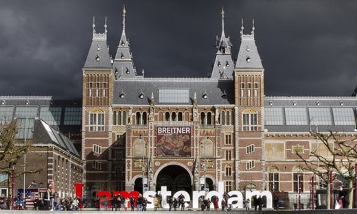 The Rijksmuseum in Amsterdam, under grey clouds.