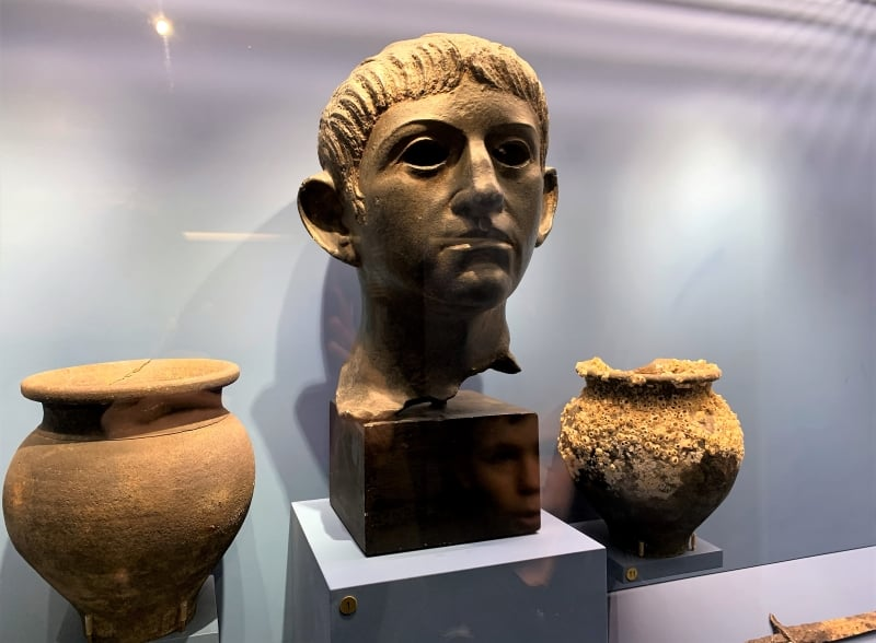 A Roman statue head with two Roman pots in a display case in Aldeburgh Museum.