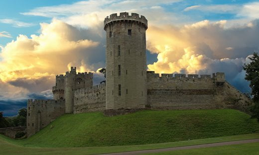 Warwick Castle against a dramatic backgrounds of clouds and sunlight.