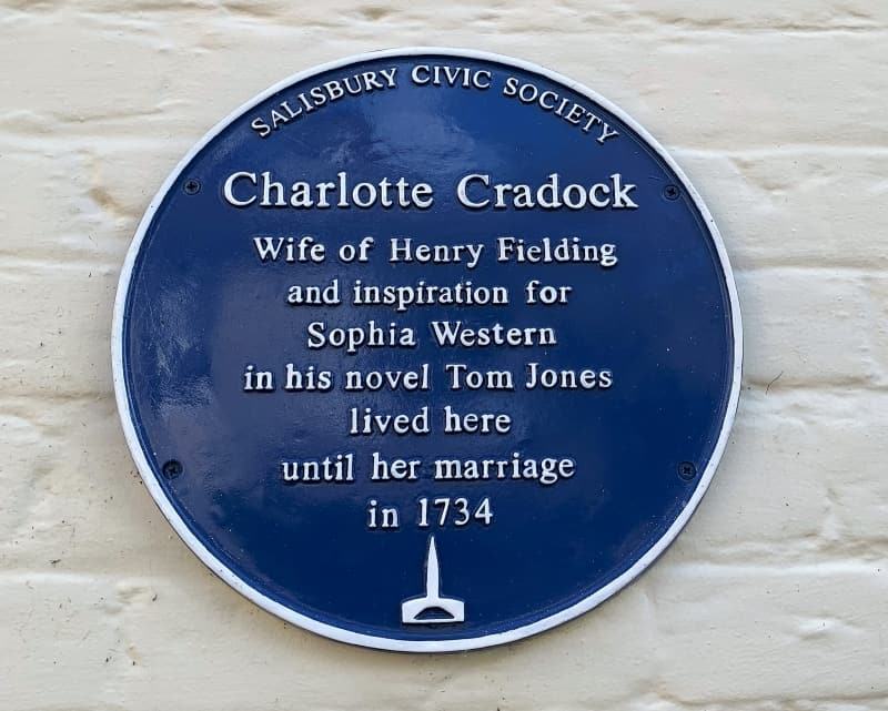 A close up of the blue plaque to Charlotte Cradock who lived in the cathedral close in Salisbury.